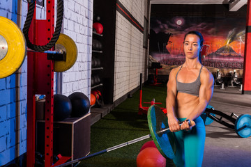 Gym girl lifting a barbell with fit body