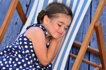 Little gir sleep in outdoor chair