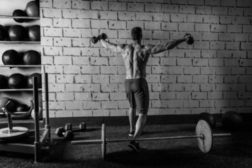 gym man rising hex dumbbells weightlifting rear