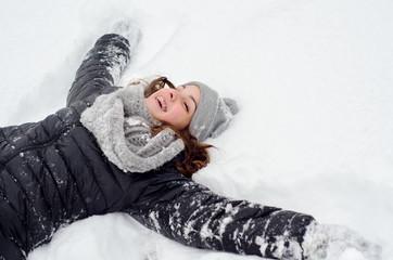 Happy teenage girl lying in the deep snow