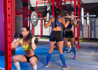 Gym women with barbell and hex dumbbell