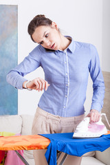 Woman checking time during ironing clothes