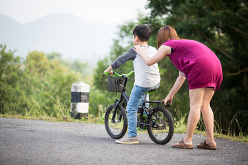 little Asian child with mother practice to riding a bicycle