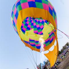 Fire heats the air inside a hot air balloon at balloon festival
