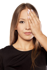 young woman closes one eye with her hand