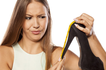 sceptical young woman measured her heels with a measuring tape