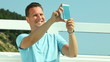 Man taking photo with smartphone by sea