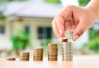 Male hand putting money coins stack like growing graph with home