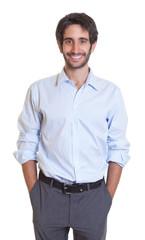 Stehender Mann mit schwarzen Haaren und Bart