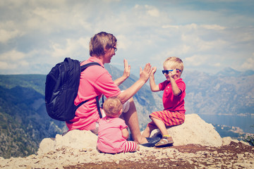 father with tow kids having fun in mountains