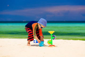 little boy playing with water on sand beach