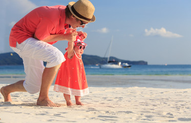 father and little daughter on the beach