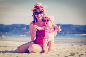 mother and little daughter on tropical beach