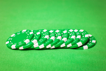 stack of poker chips on a green table