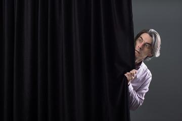 Scared man hiding behind a curtain.