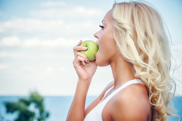 Young woman with an apple against sky background