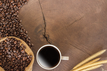coffee cup and coffee beans on wood background