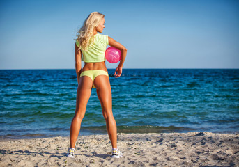 Beach woman in bikini holding a volleyball