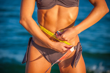 Slim fit woman at the beach in bikini with measure tape
