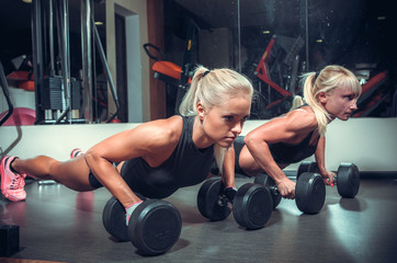 fitness women doing push up in the gym