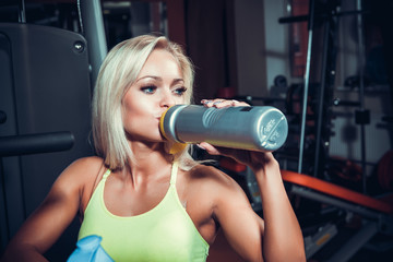 Young muscular woman drinking sports nutrition