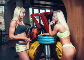 athletic young women resting during exercise in the gym
