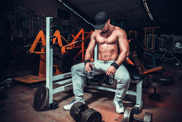 muscle shaped man tired sitting relaxed with weights and energy