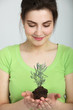 Smiling Pretty Woman Holding Small Plant