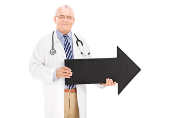 Mature doctor holding a black arrow pointing right