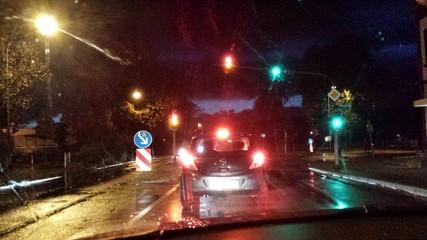 Auto steht Nachts bei Regen an der Ampel