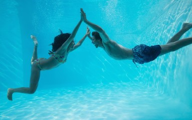 Couple holding hands and swimming underwater