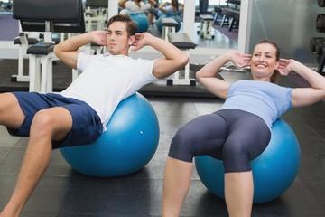 Couple doing sit ups on exercise balls