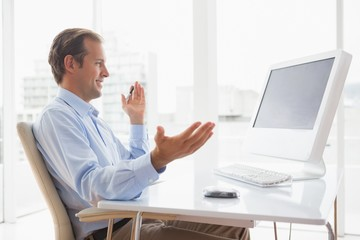 Smiling businessman sitting at his desk on video chat