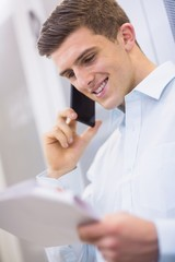 Smiling technician calling and reading a document