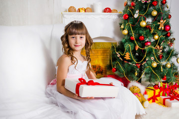 Beautiful girl near the decorated Christmas tree, holds a white