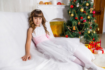 Beautiful girl near the decorated Christmas tree