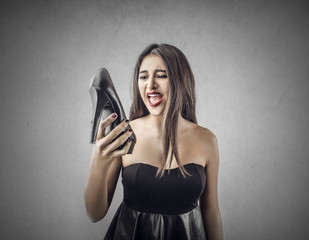Surprised girl holding a shoe in her right hand
