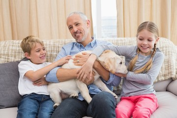 Father with his children on sofa playing with puppy