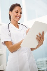 Female doctor holding clipboard in medical office