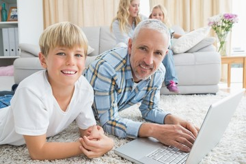 Father and son using laptop on the floor