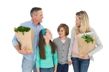 Smiling family standing holding bag of healthy groceries