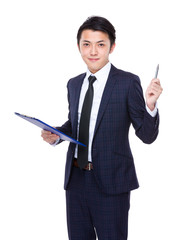 Asian businessman with clipboard and pen up