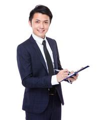 Asian businessman write on clipboard