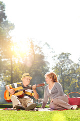Vertical shot of senior playing guitar to his wife