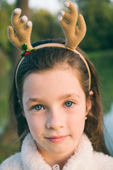 Portrait of a cute girl in reindeer antler