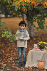in the autumn forest boy in a hat with a cup at the table