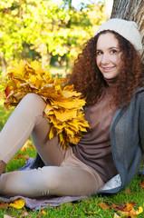 Beautiful elegant woman sitting in a park in autumn
