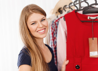 Beautiful female retail shop owner standing at clothing rack
