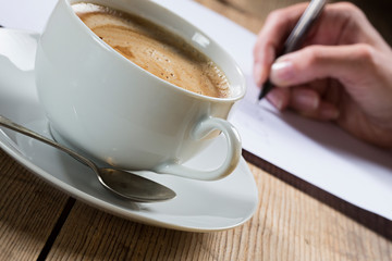 Person writing a letter with cup of coffee