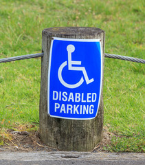 A disabled parking only sign on the street side, for providing c